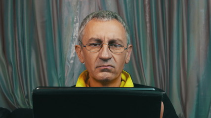 Portrait Dissatisfied Man in Glasses Reading a Tablet Computer,