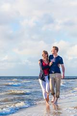 Paar rennt durch Wellen und Sand am Strand