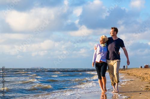 Paar rennt durch Wellen und Sand am Strand - 79526785