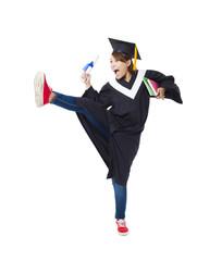 Happy female student in graduate robe dancing