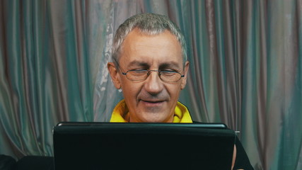 Portrait Smiling Man in Glasses Reading a Tablet Computer