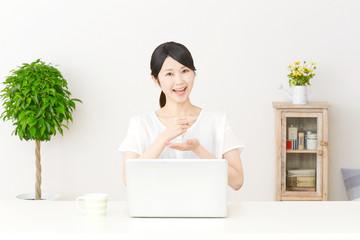 パソコンの前でひらめく女性