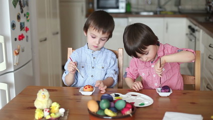 Two adorable boys, coloring eggs for Easter at home, having fun