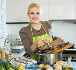 Smiling blonde woman putting pieces of lemon in fish