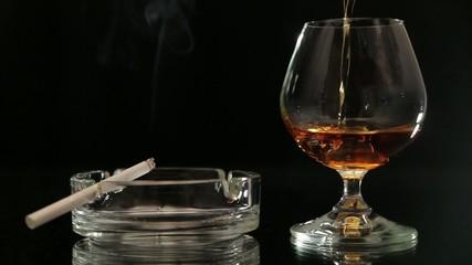 In a glass pour brandy, smokes a cigarette, black background