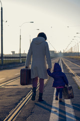 lovely girl and mother with suitcase on the railway