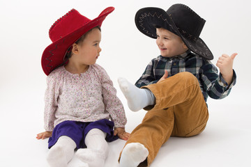 two brothers smiling wearing cowboy hats