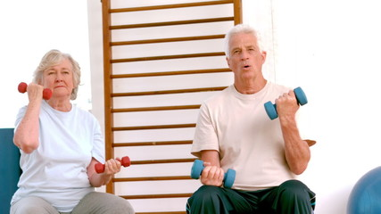 Active seniors lifting hand weights