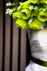 Wedding dress on a stand with green bouquet