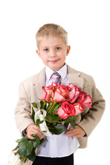 Cute little gentleman standing with big bouquet of red roses
