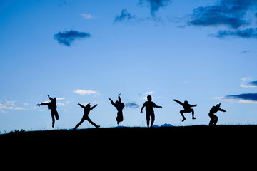 Silhouettes of six children jumping together at the blue sky