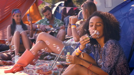 In high quality format carefree hipster blowing bubbles in tent