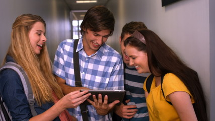 Students looking at tablet pc in the hall at the university