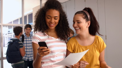 Happy students looking at smartphone at the university