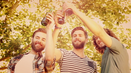 Hipsters toasting with beer bottles
