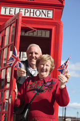 Senior couple with red telephone box in London