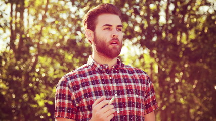 Handsome hipster smoking an electronic cigarette