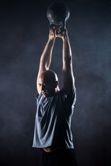 Bald charismatic athlete doing kettlebell swings.