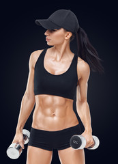 Fitness sporty woman with dumbbells, strong abs showing