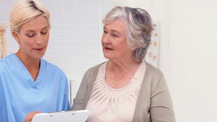 Nurse talking with elderly patient in office