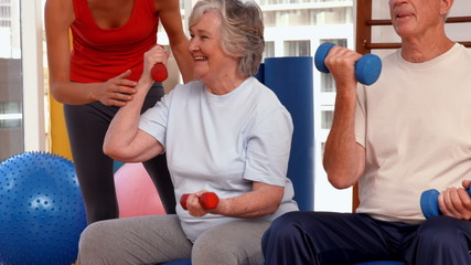 Trainer helping senior citizens work out