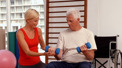 Trainer helping senior citizen work out