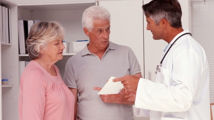 Doctor explaining prescription to elderly couple