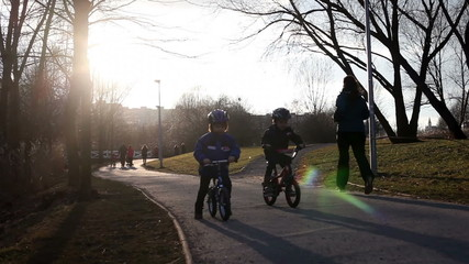 Two boys, riding bikes in the park on sunset, competing