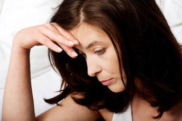 Sad depressed woman on bed.