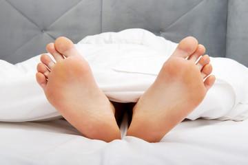 Bare woman's feet in bedroom.