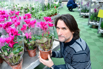 Man holding a flowers working in agreenhouse at garden center