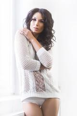 Young and beautiful brunette woman posing near the windowsill