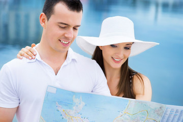 A happy couple exploring a map on the sea