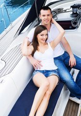A young and happy couple relaxing on a boat