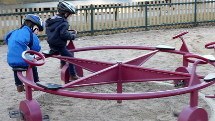 Beautiful boys, playing on a roundabout on the playground