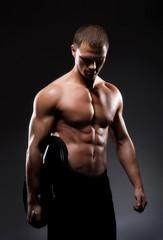 Strong bodybuilder man on a dark background