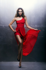 Young, beautiful and passionate woman in a long red dres