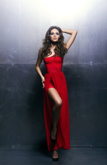 Young, beautiful and passionate woman in a long red dress
