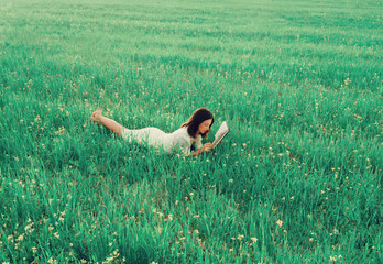Woman lying on summer meadow and reading a book