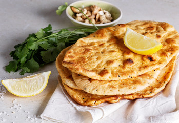 Stack of flat bread and herbs on a table