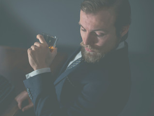 Handsome bearded man enjoying a brandy or whiskey