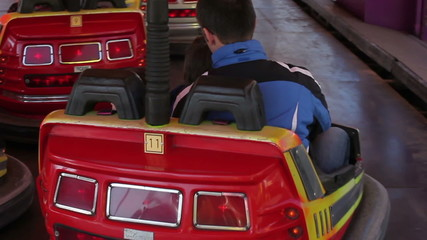Father and his two sons, going on a bumper car in amusement park