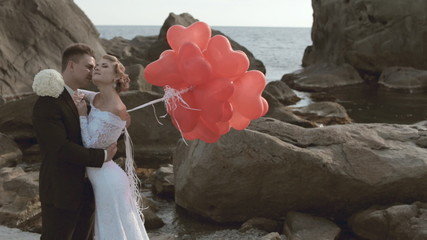 Enamoured newlyweds stand with balloons in the form of heart in