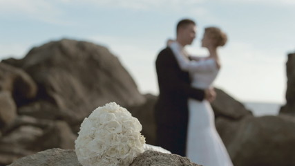 Bridal bouquet and newlyweds in love out of focus