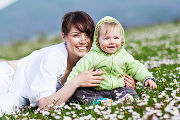 Happy mother are playing with baby in flowers field