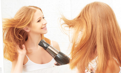 young beautiful woman dries and style your hair dryer