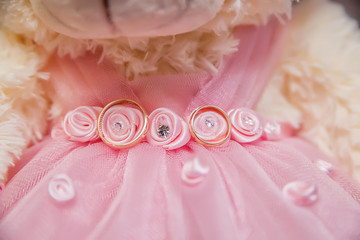 wedding rings on pink lace