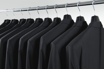 Row of men's suit jackets hanging