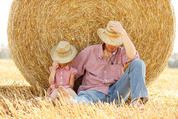 little girl with her father on the field with wheat