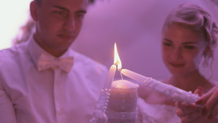 Newlyweds holding the burning candle